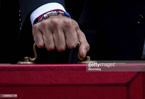 A letter block bracelet reads dada on the wrist of Rishi Sunak UK chancellor of the exchequer as he carries a dispatch box while departing from...
