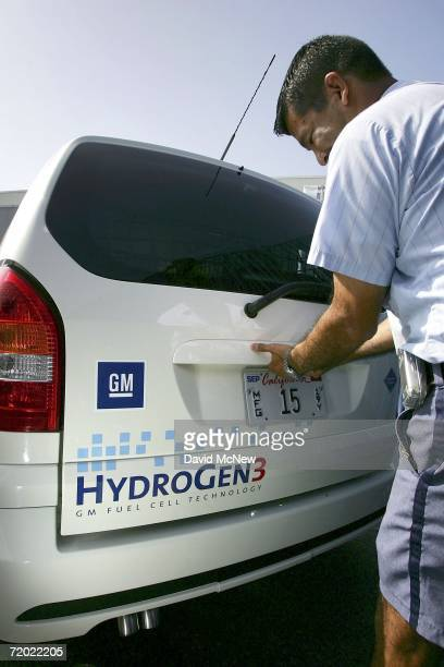 Letter carrier Aldo Vasquez opens the back of a General Motors HydroGen3 fuel cell minivan as officials unveil the new vehicle to be added to the...