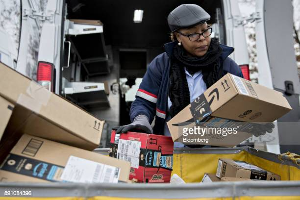 A letter carrier holds Amazoncom Inc packages while preparing a vehicle for deliveries at the United States Postal Service Joseph Curseen Jr and...