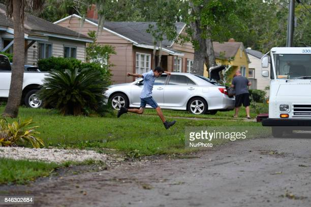 USPS letter carrier jumps over standing water as residents in the Southside neighborhood of Jacksonville FL returns on September 12 2017 after...