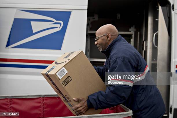A letter carrier lifts an Amazoncom Inc package from a bin while preparing a vehicle for deliveries at the United States Postal Service Joseph...