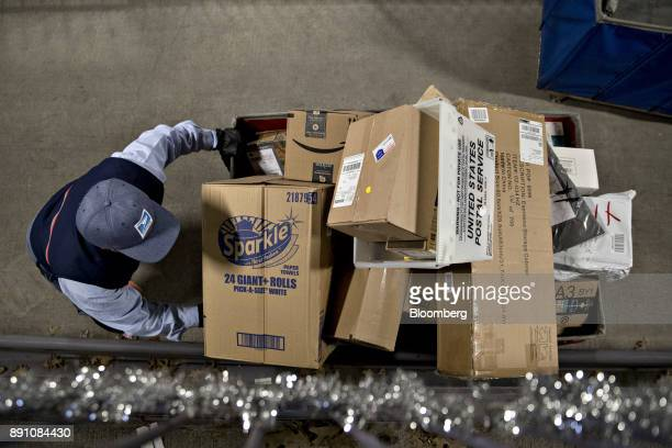 A letter carrier moves a bin full of packages for delivery at the United States Postal Service Joseph Curseen Jr and Thomas Morris Jr processing and...