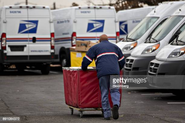 A letter carrier pushes a package bin towards a delivery vehicle at the United States Postal Service Joseph Curseen Jr and Thomas Morris Jr...