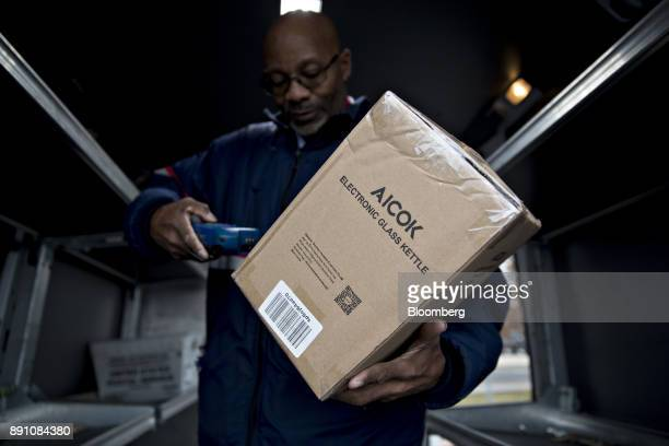 A letter carrier scans a package while preparing a vehicle for deliveries at the United States Postal Service Joseph Curseen Jr and Thomas Morris Jr...