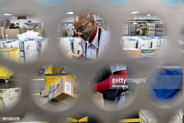 A letter carrier sorts Amazoncom Inc packages for delivery at the United States Postal Service Joseph Curseen Jr and Thomas Morris Jr processing and...