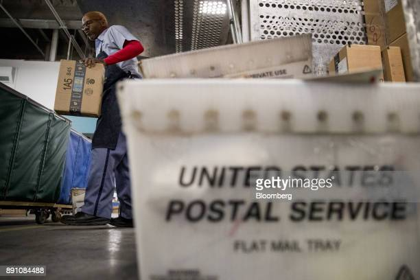 A letter carrier sorts an Amazoncom Inc package before delivery at the United States Postal Service Joseph Curseen Jr and Thomas Morris Jr processing...