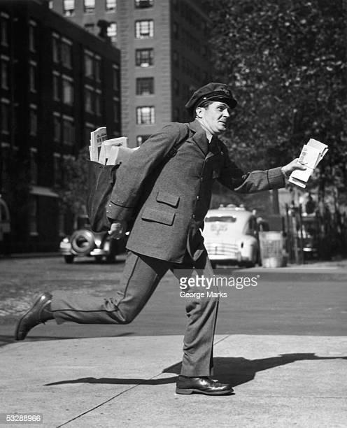 letter carrier walking down street - carteiro imagens e fotografias de stock