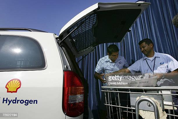 Letter carriers load mail into a General Motors HydroGen3 fuel cell minivan as officials unveil the new vehicle to be added to the U.S. Postal...
