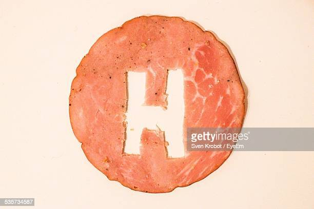 Letter H On Meat Slice Against White Background