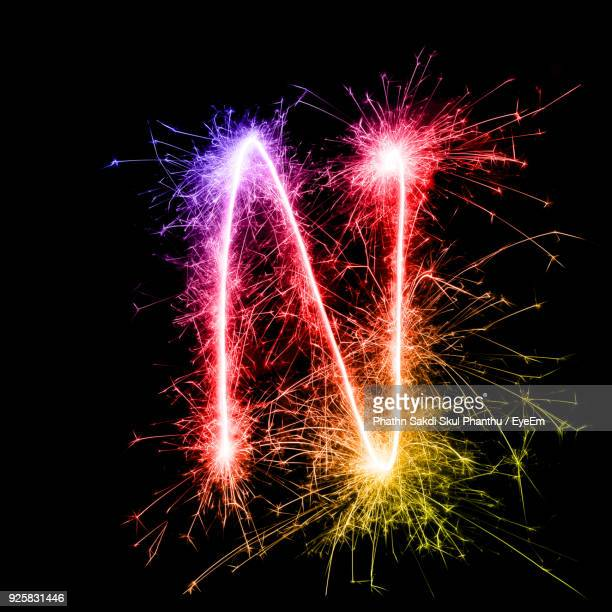 letter n made by multi colored sparklers at night - letter n stock pictures, royalty-free photos & images