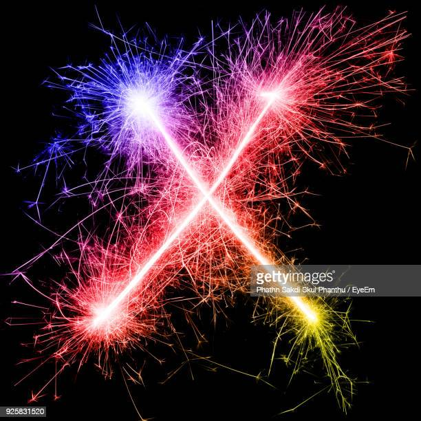 letter x made by multi colored sparklers at night - letter x stock pictures, royalty-free photos & images