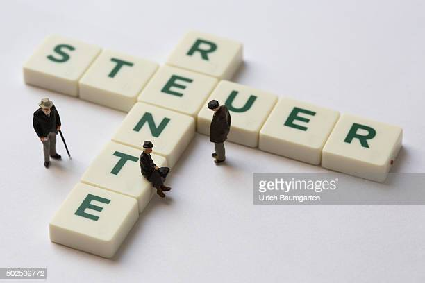 Lettering tax and pension combined from Scrabble stones with miniature figures of old people