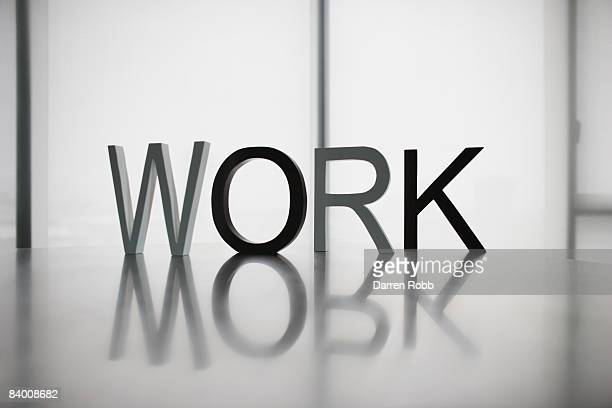 Letters on desk spelling the word WORK