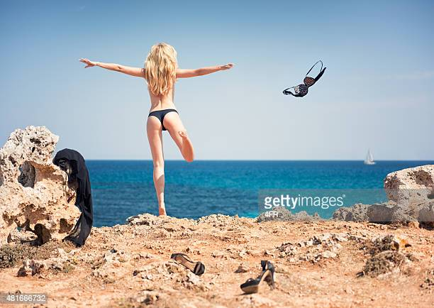 letting go, girl skinny dipping throwing away her clothes - skinny dipping stock photos and pictures