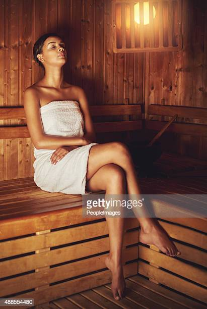 letting the sauna relax and pamper her - black woman in sauna stock pictures, royalty-free photos & images
