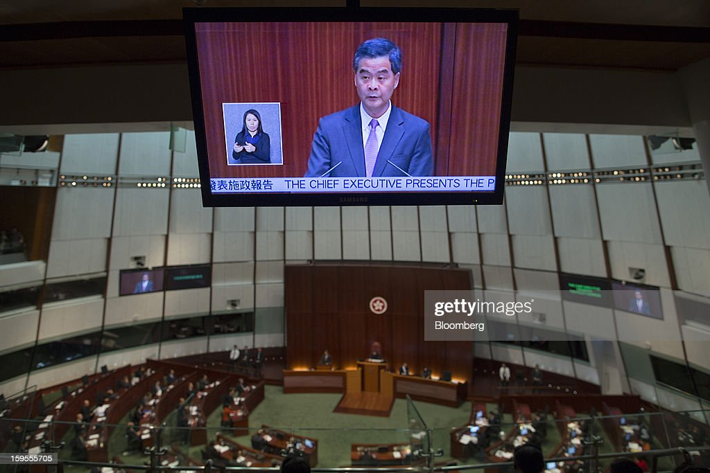 Leung Chun-ying, Hong Kong's chief executive, is shown on a television screen as he speaks in the chamber of the Legislative Council in Hong Kong, China, on Wednesday, Jan. 16, 2013. Hong Kong will maintain property curbs for overseas buyers as it seeks to meet the housing needs of its people, Leung said in his first policy address today. Photographer: Jerome Favre/Bloomberg via Getty Images