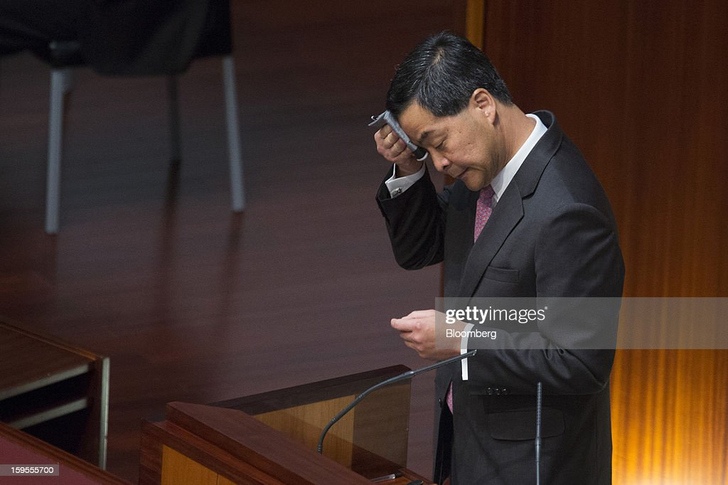 Leung Chun-ying, Hong Kong's chief executive, wipes his forehead while speaking in the chamber of the Legislative Council in Hong Kong, China, on Wednesday, Jan. 16, 2013. Hong Kong will maintain property curbs for overseas buyers as it seeks to meet the housing needs of its people, Leung said in his first policy address today. Photographer: Jerome Favre/Bloomberg via Getty Images
