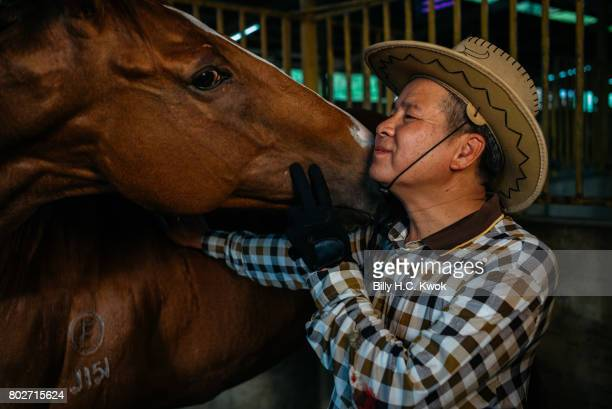 Leung Fuk Yuen Shap Pat Heung rural committee chairman and one of the indigenous leaders in the New Territories kisses his horse in his leisure park...