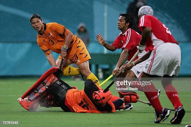 Leung Hong Wang Howard goalkeeper for Hong Kong China dives at the feet of Chua Boon Huat of Malaysia during the Men's Field Hockey Preliminary match...