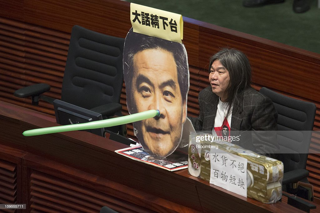 Leung Kwok-hung, a lawmaker from the League of Social Democrats, holds an effigy of Leung Chun-ying, Hong Kong's chief executive, as he speaks in the chamber of the Legislative Council in Hong Kong, China, on Wednesday, Jan. 16, 2013. Hong Kong will maintain property curbs for overseas buyers as it seeks to meet the housing needs of its people, Leung said in his first policy address today. Photographer: Jerome Favre/Bloomberg via Getty Images