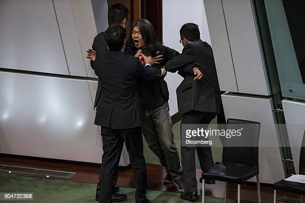 Leung 'Long Hair' Kwokhung a member of Hong Kong's Legislative Council center is removed from the chamber during the policy address of Hong Kong...
