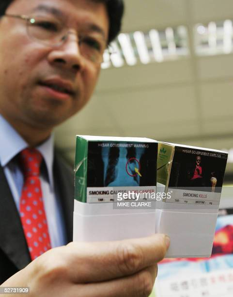 Leung Tinghung Deputy Director of Health holds up two mock packets of cigarettes showing enlarged government health warnings in Hong Kong 29 April...