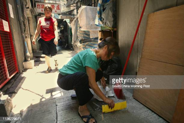 Leung Wahhing who has been doing her bussiness more than twenty years in Mongkok cleaning up the back alley in front of her shop on Shan Tung street...