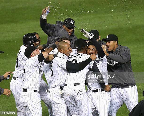 Leury Garcia of the Chicago White Sox is mobbed by teammates including Alexei Ramirez and Moises Sierra after hitting a gamewinning walkoff single in...