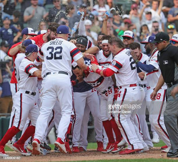 Leury Garcia of the Chicago White Sox is mobbed by teammates as he comes to the plate after hitting a walk-off, solo home run in the 9th inning...