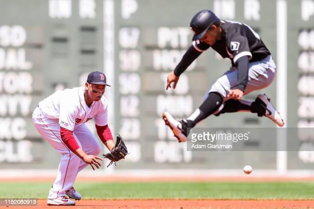 Leury Garcia of the Chicago White Sox jumps out of the way as Rafael Devers of the Boston Red Sox fields a ground ball in the first inning of a game...