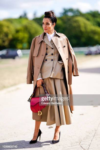 Levante wears a beige trench coat a blazer button jacket a pleated skirt a red Saddle bag from Dior outside Dior during Paris Fashion Week Womenswear...