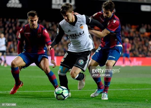 Levante's defender Coke and Levante's defender Rober Pier vies with Valencia's Argentinian forward Luciano Vietto during the Spanish league football...