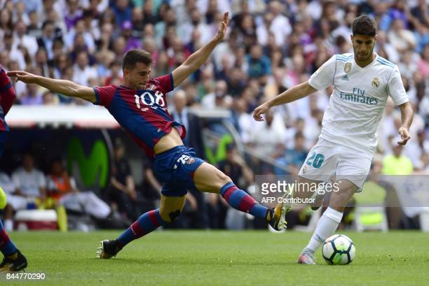 Levante's defender Sergio Postigo vies with Real Madrid's midfielder Marco Asensio during the Spanish Liga football match Real Madrid vs Levante at...