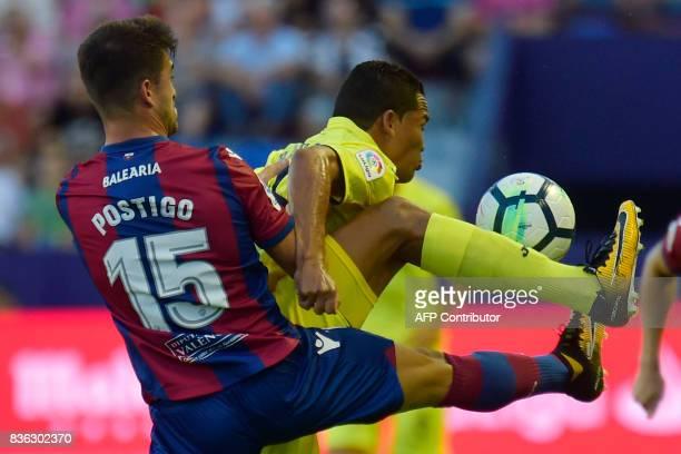 Levante's defender Sergio Postigo vies with Villarreal's Colombian forward Carlos Bacca during the Spanish league footbal match Levante UD vs...