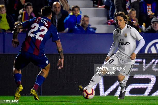 Levante's Spanish defender Antonio Luna challenges Real Madrid's Croatian midfielder Luka Modric during the Spanish league football match between...