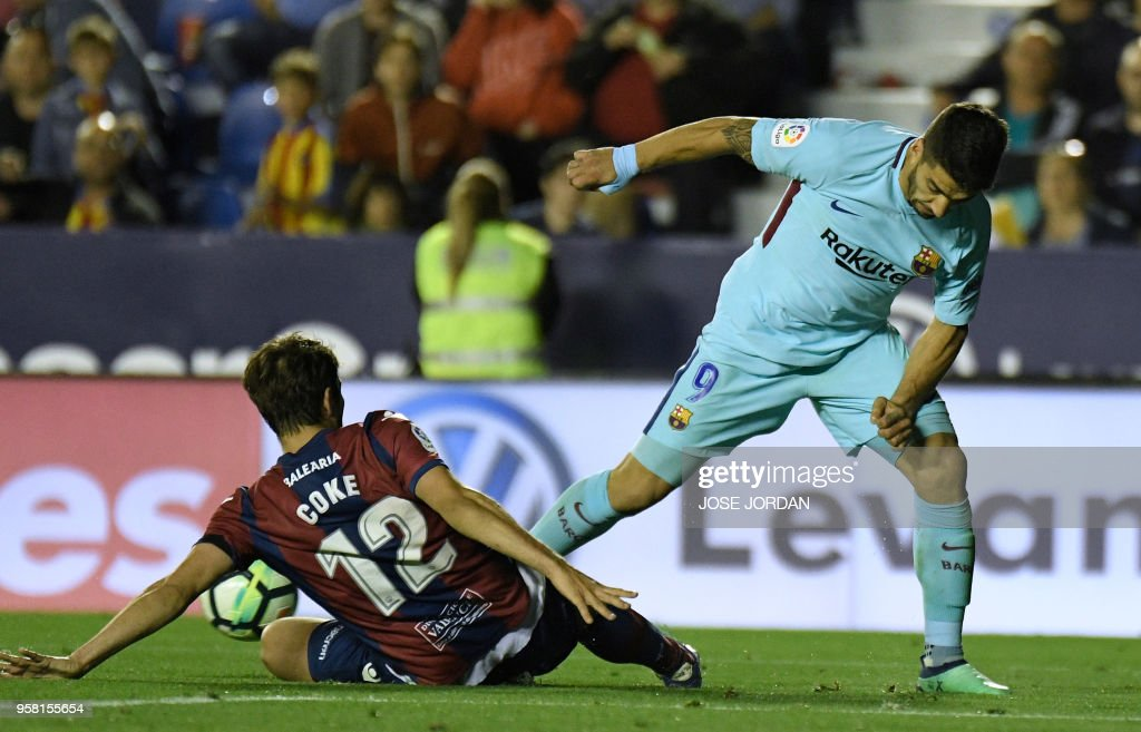 Levante's Spanish defender Coke (L) vies with Barcelona's Uruguayan forward Luis Suarez during the Spanish league football match between Levante and Barcelona at the Ciutat de Valencia stadium in Valencia on May 13, 2018.