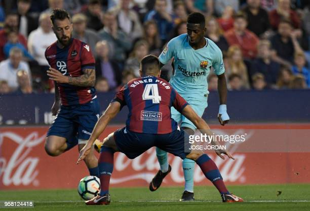 Levante's Spanish defender Rober Pier and Levante's Spanish defender Antonio Luna vie with Barcelona's French forward Ousmane Dembele during the...
