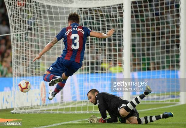 TOPSHOT Levante's Spanish defender Tono Garcia jumps for the ball with Real Betis' Spanish goalkeeper Pau Lopez during the Spanish league football...