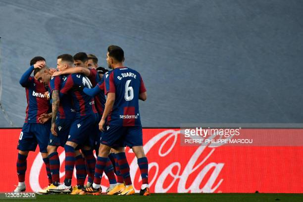 Levante's Spanish forward Roger Marti is congratulated after scoring his team's second goal during the Spanish league football match Real Madrid CF...