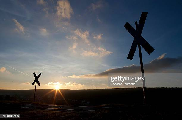 A level crossing is illuminated by the rising sun on October 29 2010 in Martinroda Germany