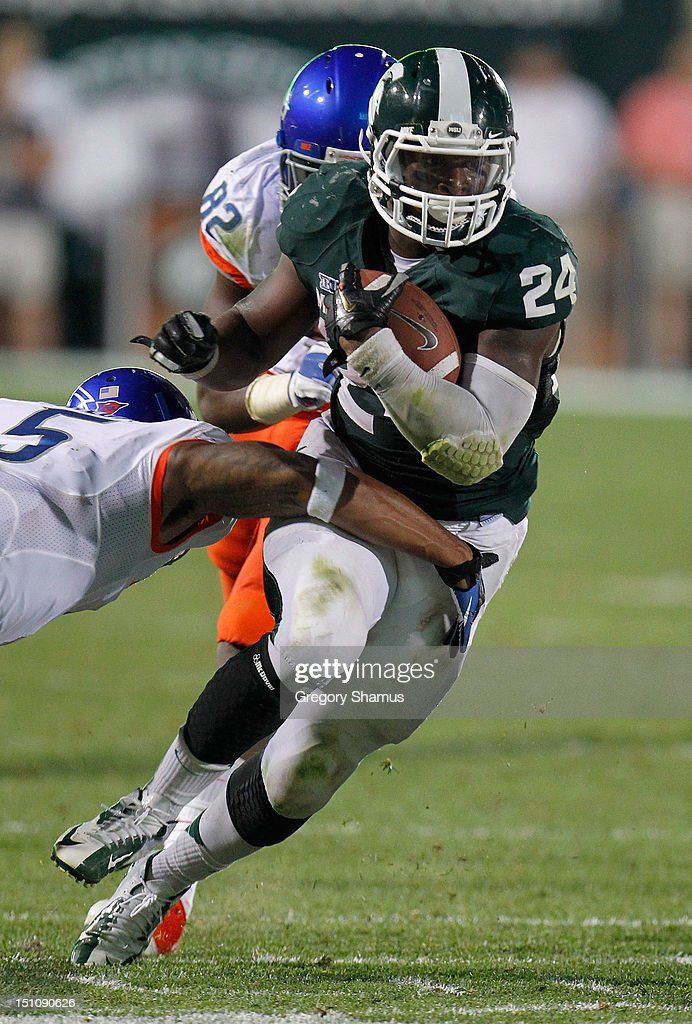 Le'Veon Bell #24 of the Michigan State Spartans looks for running room between Jamar Taylor #5 and Samuel Ukwuachu #82 of the Boise State Broncos at Spartan Stadium on August, 2010 in East Lansing, Michigan. Michigan State won the game 17-13.