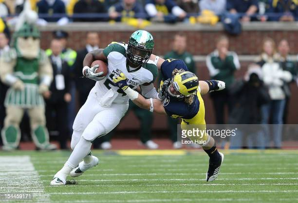 Le'Veon Bell of the Michigan State Spartans runs for a short gain as Brennen Beyer of the Michigan Wolverines makes the stop during the first half of...