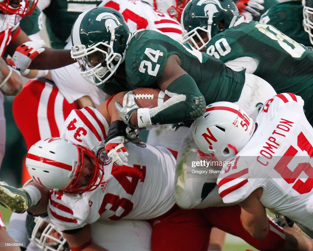 Le'Veon Bell #24 of the Michigan State Spartans tries to split the tackles of Cameron Meredith #34 and Will Compton #51 of the Nebraska Cornhuskers during a third quarter run at Spartan Stadium Stadium on November 3, 2012 in East Lansing, Michigan. Nebraska won the game 28-24.