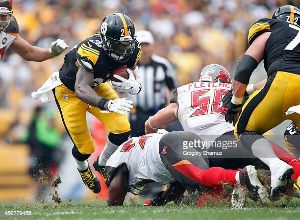 Le'Veon Bell of the Pittsburgh Steelers avoids a tackle by Adrian Clayborn of the Tampa Bay Buccaneers during the second quarter at Heinz Field on...
