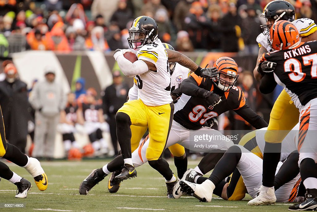 Le'Veon Bell #26 of the Pittsburgh Steelers breaks through the line of scrimmage while carrying the ball during the fourth quarter of the game against the Cincinnati Bengals at Paul Brown Stadium on December 18, 2016 in Cincinnati, Ohio. Pittsburgh defeated Cincinnati 24-20.