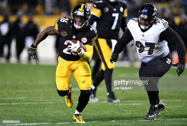 Le'Veon Bell of the Pittsburgh Steelers carries the ball against Michael Pierce of the Baltimore Ravens in the second half during the game at Heinz...