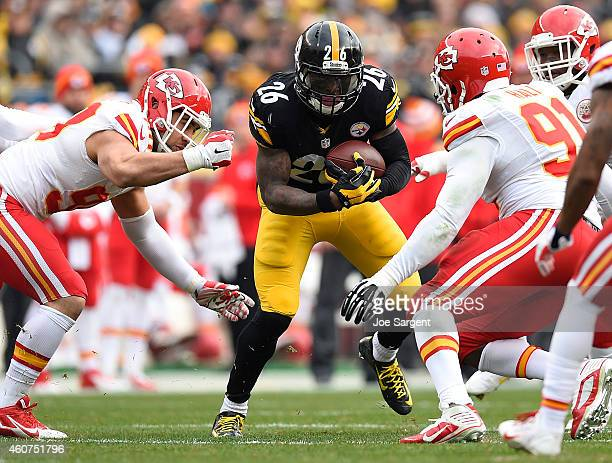 Le'Veon Bell of the Pittsburgh Steelers carries the ball between the defense of Tamba Hali and Nick Williams of the Kansas City Chiefs during the...