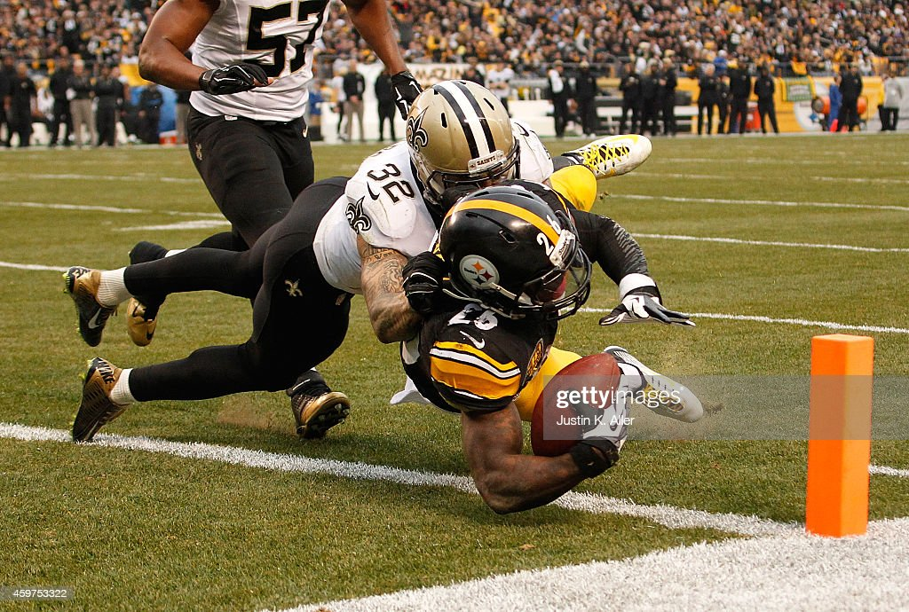Le'Veon Bell #26 of the Pittsburgh Steelers carries the ball for a touchdown in front of Kenny Vaccaro #32 of the New Orleans Saints during the third quarter at Heinz Field on November 30, 2014 in Pittsburgh, Pennsylvania.