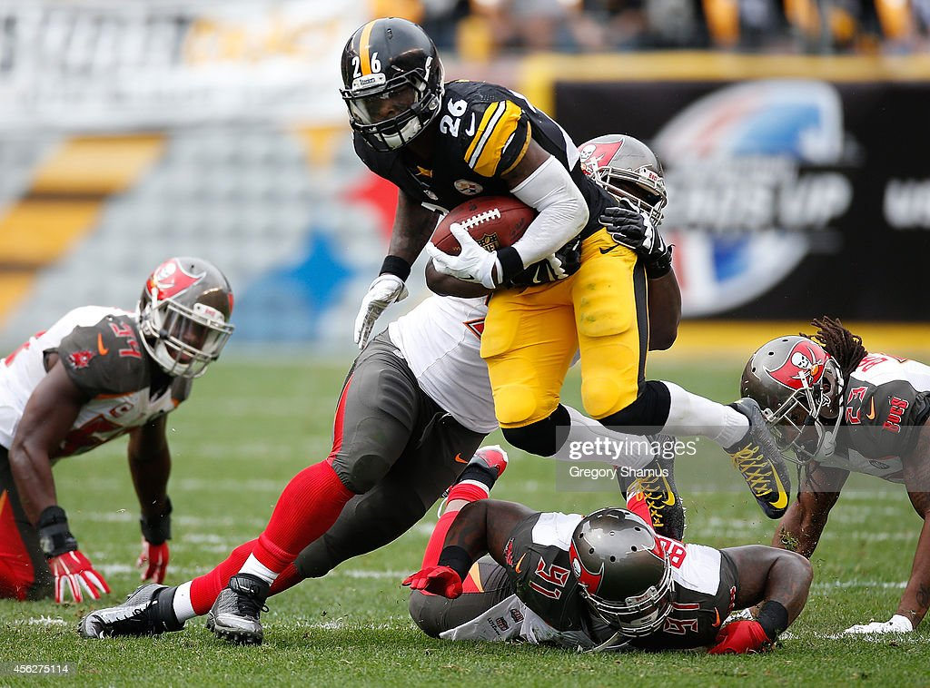 Le'Veon Bell #26 of the Pittsburgh Steelers carries the ball in front of the defense of Clinton McDonald #98 and Da'Quan Bowers #91 of the Tampa Bay Buccaneers at Heinz Field on September 28, 2014 in Pittsburgh, Pennsylvania.