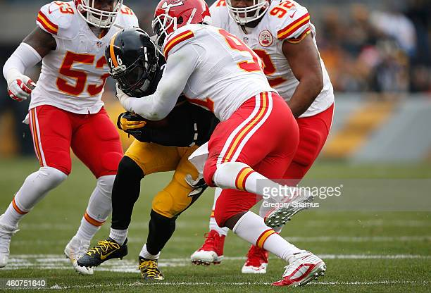 Le'Veon Bell of the Pittsburgh Steelers gets tackled by Tamba Hali of the Kansas City Chiefs during the second quarter at Heinz Field on December 21,...